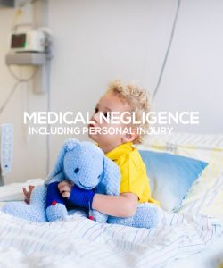 Little boy on hospital bed holding blue toy elephant