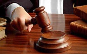 Judge hitting gavel against wooden sound block