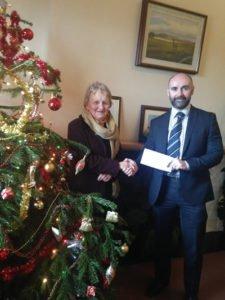John Kelly giving donation to SVDP representative beside Xmas Tree
