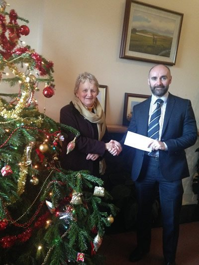 John Kelly giving donation to SVDP representative beside Xmas Tree