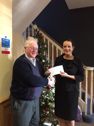 Niamh Ni Mhurchu handing donation to SVDP
