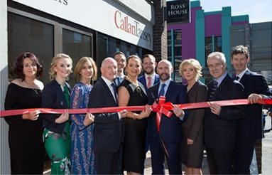 Callan Tansey staff opening Galway office with red ribbon