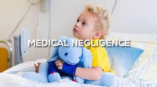 Boy on hospital bed holding blue toy elephant