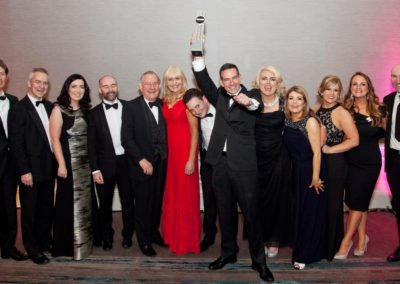 Roger Murray holding Law Firm of the Year award with staff at the awards